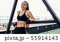 Smiling woman in sportswear leaning on power rack  55914143