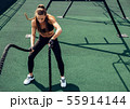 Young muscular woman exercising with battle ropes  55914144