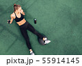 Tired female athlete sitting on a terrace floor  55914145