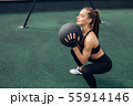 Side view of woman squatting with a medicine ball  55914146
