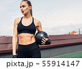 Woman in fitness wear standing outdoors  55914147