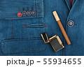 Cigar and a lighter lie on a denim jacket. Fashion 55934655