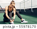 Woman in sports wear tie shoelaces while sitting  55978170