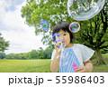 新緑の公園でシャボン玉を吹く女の子 55986403