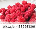 Close-up ripe juicy and delicious raspberry in a plastic transparent dish on a light background 55995809