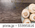 Close-up of white mushrooms on a white plate on a dark wooden table. Vegetarian healthy food 55995816
