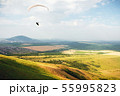 A paraglider flies in the sky in a cocoon suit on a paraglider over the Caucasian countryside with 55995823
