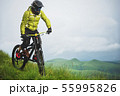 Front view of a man on a mountain bike standing on a rocky terrain and looking down against a gray 55995826