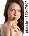 Young girl sucking lollipop and looking at the 56047607
