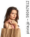 Young caucasian white girl holding paper bag with 56047612