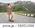 A stylish young man standing along a winding mountain road with a skate or longboard in his hands 56051566