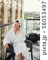 Health and body treatment. Portrait of young smiling woman in white bathrobe sitting on chair at 56053497