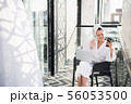Young pretty woman in white soft bathrobe making selfie while relaxing on chair on outdoor terrace 56053500