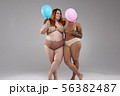 Couple of fat female friends posing for camera against grey background 56382487