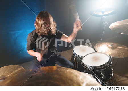 Portrait of a long-haired drummer with chopsticks in his hands sitting behind a drum set. Low key 56617238