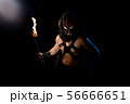 Shirtless man in wolf mask with torch in the dark 56666651
