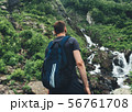 Young man looking at mountain stream in the forest admires nature. 56761708