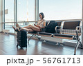 Woman resting in arrival hall waiting for a transfer at airport 56761713