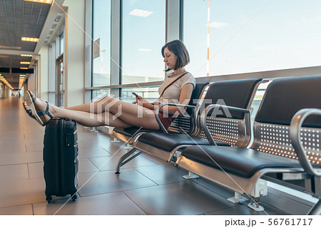 Female tourist sitting on bench with baggage in waiting room at airport. 56761717