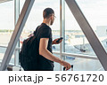 Young woman standing near window at airport holding mobile phone 56761720