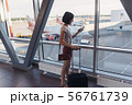 Young woman standing near window at airport holding mobile phone 56761739