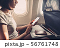 Young woman on a plane with a smartphone in her hands 56761748