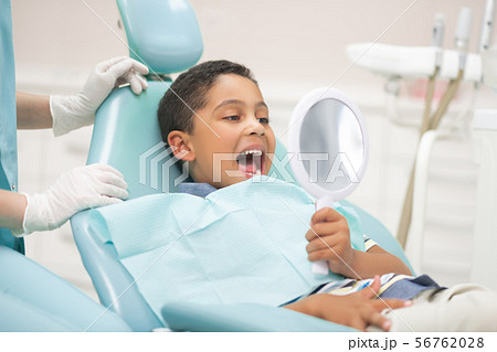 Boy opening mouth and looking into mirror while visiting dentist 56762028