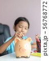 Happy little asian girl putting money coin into 56768772
