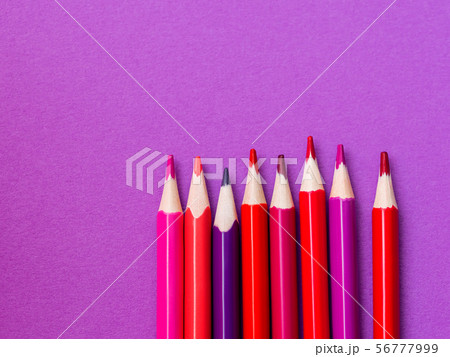 Vertical row of red and magenta pencils on purple 56777999