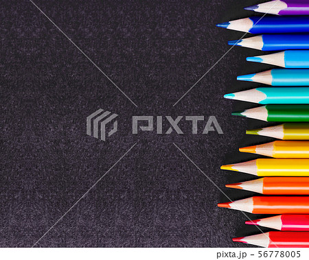 Row of colorful watercolor pencils on black 56778005
