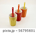 Three colored ceramic glasses with spoons 56795601