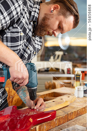Portrait of craftsman working in workshop with guitar 56856868