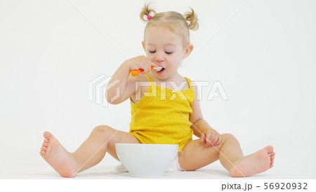 Baby girl eating her breakfast with a spoon on white background 56920932