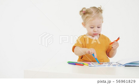 Baby girl coloring unrecognizable picture with crayons on white background 56961829
