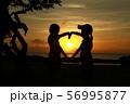海に沈む夕陽の空と少女たちのハートのシルエット 56995877