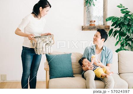 赤ちゃんにミルクを飲ませる父親と家事をする母親 57024397