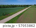 Aerial view of gravel road on farmland fields in spring 57053862