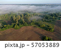 Plowed farm field by summer end forest with mist, aerial 57053889