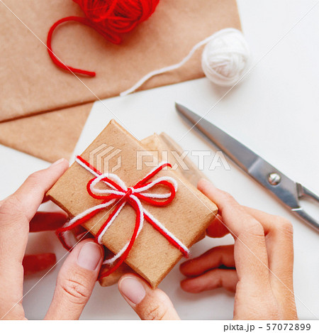 Woman is packing Christmas and New Year DIY presents in craft paper with ribbon 57072899
