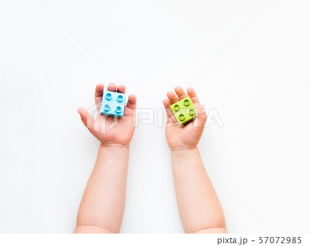 Child is playing with colorful constructor blocks. 57072985