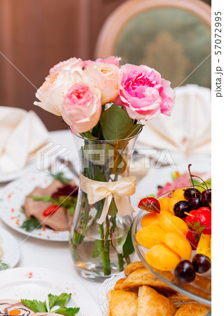 Table set for wedding banquet with floral composition of decorative roses. Floral decoration in tall vase. 57072995