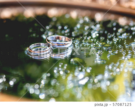 Pair of wedding rings on wet mirror surface with green reflection. Close up photo with traditional jewelry of bride and groom. 57087125