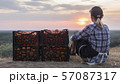 Woman farmer sitting near boxes with tomatoes, admiring the beautiful landscape, resting after work 57087317