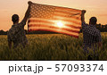 Two men energetically raised the US flag in a picturesque field of wheat 57093374