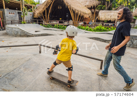 Athletic boy learns to skateboard with a trainer in a skate park. Children education, sports 57174604