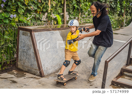 Athletic boy learns to skateboard with a trainer in a skate park. Children education, sports 57174999