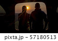 A man and a woman admire the beautiful sunset from the trunk of a car 57180513