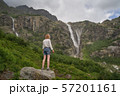 Woman standing on the rock and enjoying the view of epic waterfall  57201161