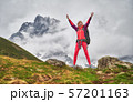 Happy hiking woman with backpack standing with rise up hands in mountain area. 57201163