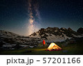 Hiker standing near tent and looking at the milky way in mountains at night 57201166